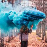 Colored smoke bomb in front of a woman under an umbrella