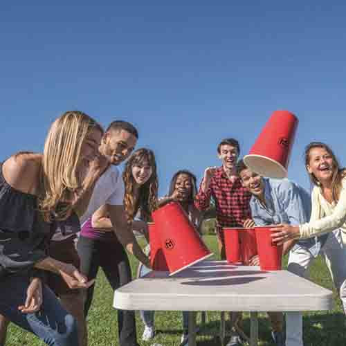 Giant Beer Pong Cups featuring a group of men and women flipping giant cups